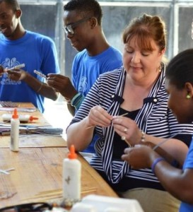 Stephanie learning to make beads for the Trades of Hope bracelets while in Haiti.
